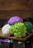 Fresh organic white and purple cauliflower, broccoli, romanesco. In wooden bowl Stock Photos