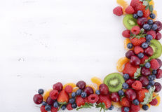 Fresh organic wholesome fruit on white wood table.