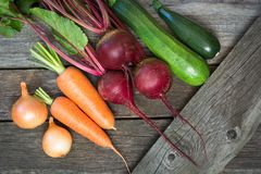 Fresh organic zucchini, beet and carrot on the wooden table. Fresh organic zucchini, onion, beet and carrot on the wooden table.Top view Stock Photo