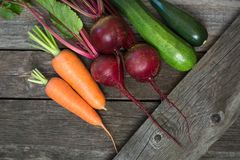 Fresh organic zucchini, onion, beet and  carrot on the wooden table. Fresh organic zucchini, onion, beet and carrot on the wooden table.Top view Royalty Free Stock Images
