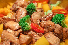 Fresh oriental chicken stir-fry. Sesame chicken stir-fry with yellow and red ppeppers, cashew nuts and broccoli Royalty Free Stock Image