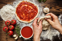 Fresh original Italian raw pizza preparation. Close-up of man hands in action Royalty Free Stock Images