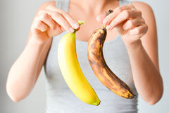 Fresh and overripe bananas on woman hand. Woman comparing an overripe banana and a fresh one stock photo