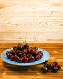 Fresh Overripe ripe Cherries on Blue Rustic Wooden Background. Round blue plate of fresh ripe cherries on old wooden background for design montage. Vintage wood stock photo