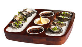Fresh oyster appetiser on white. Fresh oysters served on appetiser tray with lemon wedges and dipping sauce isolated on white background Stock Images