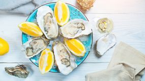 Fresh oysters close-up on blue plate, served table with oysters, lemon and champagne in restaurant. Gourmet food. Tabletop view Stock Photography