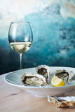 Fresh oysters and a glass of wine. Fresh oysters with lemon on plate and a glass of wine in the wood table Royalty Free Stock Photography