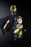 Fresh oysters with lemon and a glass of wine on a dark backgroun. D Stock Photo