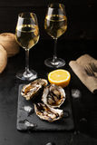 Fresh oysters with lemon and a glass of wine. On a dark background Stock Photos
