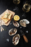 Fresh oysters with lemon and a glass of wine. On a dark background Royalty Free Stock Image