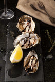 Fresh oysters with lemon and a glass of wine. Fresh oysters with lemon and glasses of wine on a dark background Royalty Free Stock Images