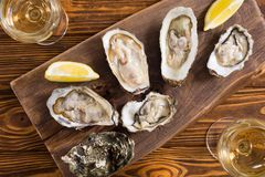 Fresh Oysters with lemon and white wine. Seafood background royalty free stock image