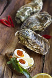 Fresh oysters with red caviar and chili pepper Stock Photography