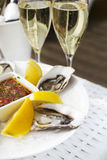 Fresh oysters shell with lemon and glasses of champagne. Top of. Selective focus point on fresh oysters shell with lemon and glasses of champagne Stock Images