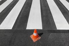 Crosswalk repairing and painting, road and traffic cone. Fresh painted  pedestrian crosswalk at a street with traffic cone Royalty Free Stock Image