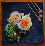 Fresh Palm Salad with Prawn Skewers in a glass on a black square plate with top down view Royalty Free Stock Photos