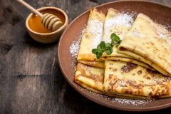 Fresh pancakes with fragrant maple syrup and honey. Russian holiday pancake week. crepes with honey or syrup.  stock photography