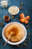 Fresh pancakes with honey, maple syrup, cottage cheese and tangerines. Wooden background. Top view. Selective focus royalty free stock images