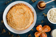 Fresh pancakes with honey, maple syrup, cottage cheese and tangerines. Wooden background. Top view. Selective focus royalty free stock photo