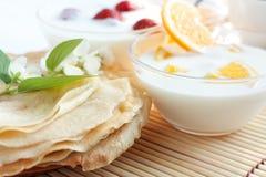 Fresh pancakes and orange yogurt. Delicious and easy breakfast Royalty Free Stock Photo
