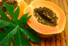 Fresh papaya halves and green leaf Royalty Free Stock Images