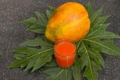 Fresh papaya juice in the glass with papaya fruits and leaf. Fresh papaya juice in the glass with papaya fruits and papaya leaf on black stone table.Raw food Stock Photos