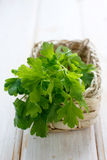 Fresh parsley. In the basket on white wooden table Stock Image