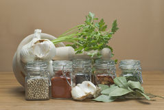 Fresh parsley and dry spices. Mortar and pestle with fresh parsley and some jars with spices on a wooden surface Stock Photo