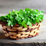 Fresh parsley sprigs in a wicker basket and on a wooden background. Garden parsley. Rich source of anti-oxidant nutrients Stock Images