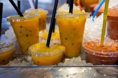 Fresh passiflora juice in ice  at farmers market. Fresh cold yellow passiflora juice in ice  at farmers market stock image