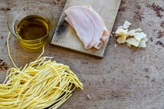 Fresh pasta. Close up of  row  fresh  spaghetti pasta , parmesan cheese,     , olive oil extra vergin,  ham .spaghetti and ingredients. Italian healthy food Royalty Free Stock Images