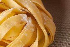 Fresh Pasta. Close-up texture of Home made tagliatelle pasta flour ribbon noodle Stock Image