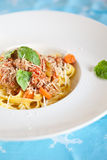 Fresh pasta dish. Delicious pasta dish with bolognese sauce and basil Stock Photo