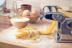 Fresh pasta and pasta machine. On kitchen table Stock Images