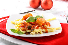 Fresh pasta with pork rind, tomato and basil. On on the Christmas table Royalty Free Stock Photos