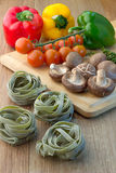 Fresh pasta with raw ingredients. Mushroom tomato fresh pepper sweet pepper on wooden board Stock Image