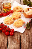 Fresh Pasta on Table with Cheese, Tomatoes and Oil Royalty Free Stock Image