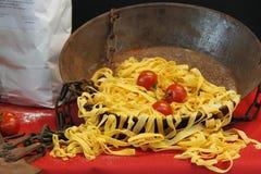 Fresh pasta with tomatoes. Machine to make the Italian pasta royalty free stock image
