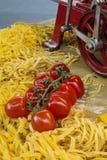 Fresh pasta with tomatoes. Machine to make the Italian pasta stock images