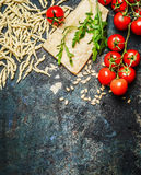 Fresh pasta  with tomatoes,parmesan and arugula on rustic background, top view, border Stock Photography