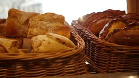 Fresh pastries in a basket on showcase, in the store. Sun rays through pastries