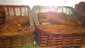 Fresh pastries in a basket on showcase, in the store. Sun rays through pastries stock video