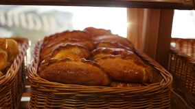 Fresh pastries in a basket on showcase, in the store. Sun rays through pastries stock footage