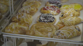 Fresh pastries are placed in sale case. View of fresh pastries being placed in case stock video