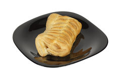 Fresh pastries puff pastry lying on a black plate. Fresh bun of puff pastry lying on a black plate Royalty Free Stock Image