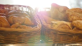 Fresh pastries in a basket on showcase, in the store. Sun rays through pastries stock video footage