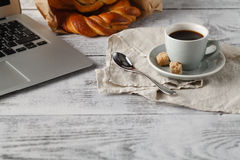 Fresh pastry and cup of brew coffee on table in office with lapt Stock Photography