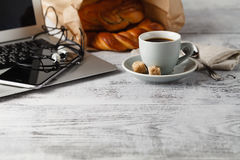 Fresh pastry and cup of brew coffee on table in office with lapt Royalty Free Stock Photo
