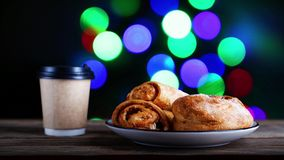 Fresh pastry and paper cup of coffee. On wooden table against colorful flashing lights on blurred background. Shallow focus stock video footage