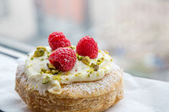 Fresh Pastry with Raspberries and Pistachios. Puff pastry tart with powdered sugar, pistachio cream and raspberries in window Stock Photos
